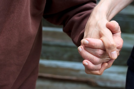 Holding senior ladys hand in front of staircase Stock Photo