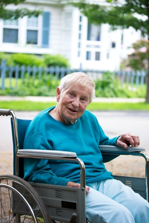 Happy senior lady in wheelchair in front of house