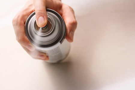 aerosol can: Hand spraying white spray paint Stock Photo