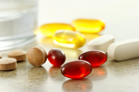 supplements: Supplement capsules and glass of water Stock Photo