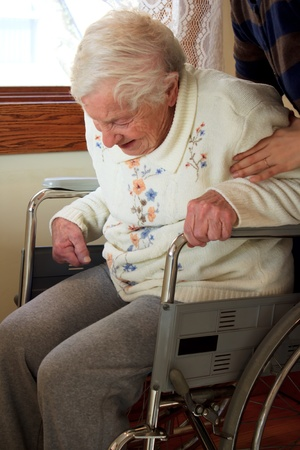 aging: Caregiver helping senior lady get up from wheelchair Stock Photo