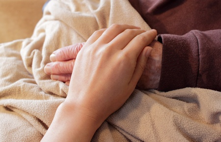 Old and Young Hands on Brown Blanket photo