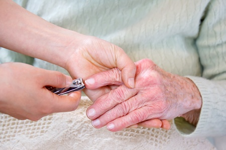 home health care: Helping senior woman cutting her fingernails Stock Photo