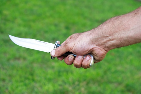 Man holding dagger over green lawn background photo