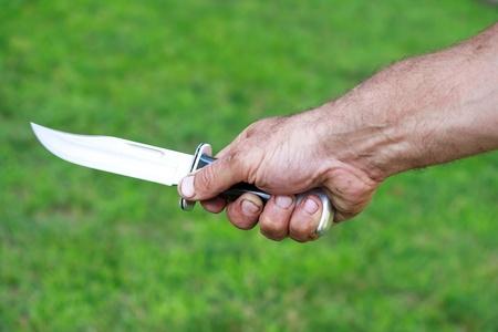 dangerous man: Man holding dagger over green lawn background