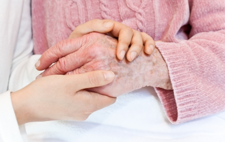 blankets: Caregiver holding seniors hand