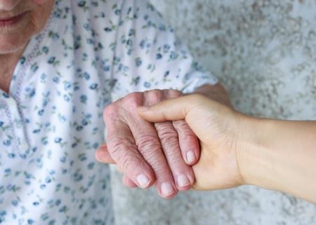 age care: Caregiver holding seniors hand