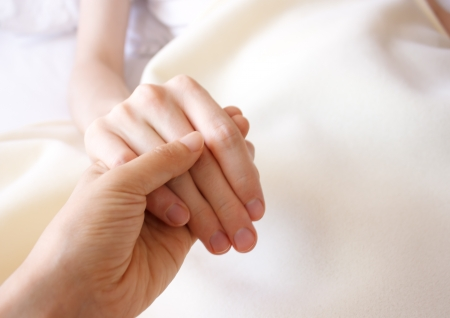 heal care: Holding the hand of a sick loved one in hospital bed