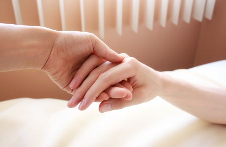 to clasp: Holding the hand of a sick loved one in hospital bed