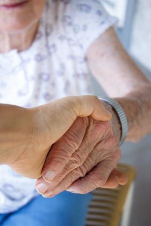 aged: Caregiver holding seniors hand