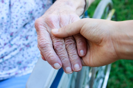 old age care: Caregiver holding seniors hand in wheelchair