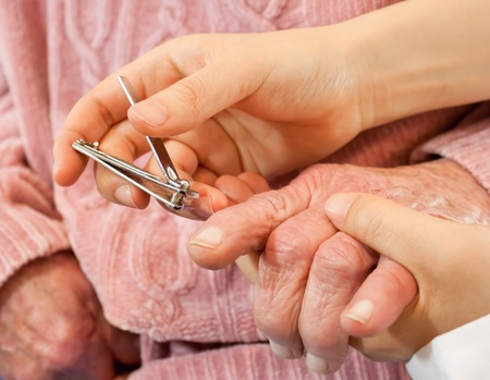 medical personal: Helping senior woman cutting her nails Stock Photo