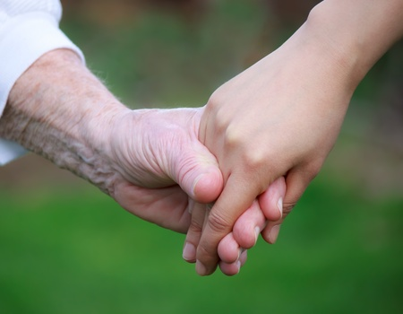 caregiver: Young and senior women holding hands
