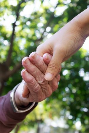 Senior en jonge vrouwen hand in hand Stockfoto