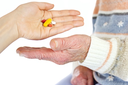 Giving pills to elderly woman photo