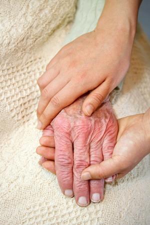 artrite: Mani vecchi e giovani sulla coltre bianca Archivio Fotografico