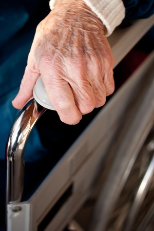 Senior womans hand on a wheelchair