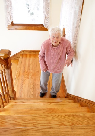 banister: Senior woman infront of staircase