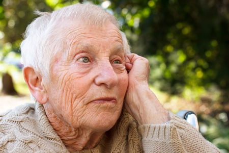 Pensive senior lady in wheelchair outside photo