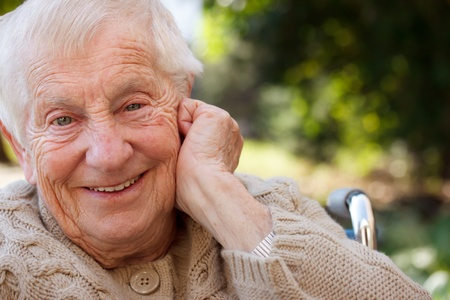 aging woman: Happy senior lady in wheelchair smiling outside Stock Photo