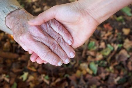 personnes �g�es: Jeunes et seniors se tenir la main sur les feuilles d'automne Banque d'images