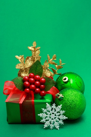 Christmas green gift box with ornaments on green background photo