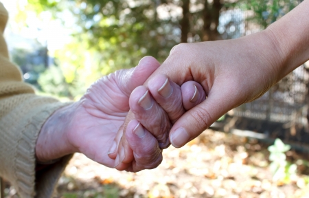 Houden van jonge en senior handen in de herfst Stockfoto