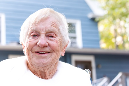 80 plus years: Happy senior lady in front of blue house