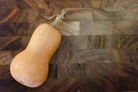 Butter nut squash on wooden cutting board photo
