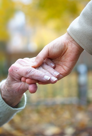 old age care: Young and senior holding  hands in autumn Stock Photo