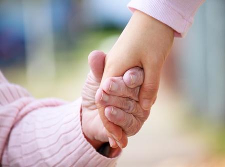 personas ayudando: Tomarse de las manos mayores y los jóvenes fuera de