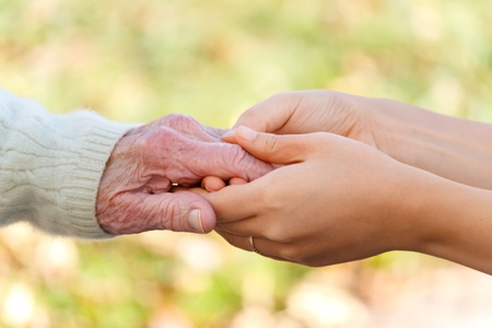 old age care: Senior and young holding hands outside