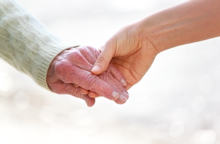 Senior and young holding hands over shiny white background photo
