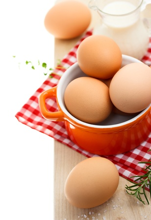 Fresh brown eggs with milk on red gingham checked tablecloth Imagens