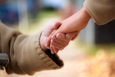 personnes �g�es: Seniors et les jeunes se tenir la main en dehors de Banque d'images