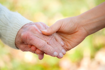 caregiver: Senior and young holding hands outside