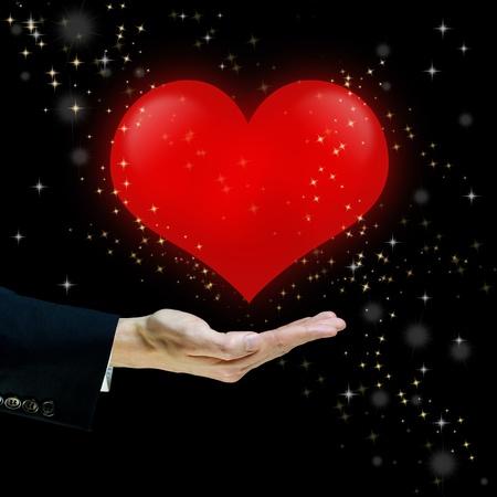 corazon en la mano: Coraz�n rojo flotando sobre una mano sobre fondo negro con polvo de estrellas Foto de archivo