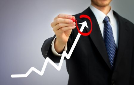 successful business: Businessman highlighting business growth on a graph Stock Photo