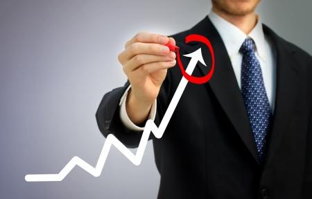 Zakenman markeren groei van de activiteiten op een grafiek Stockfoto