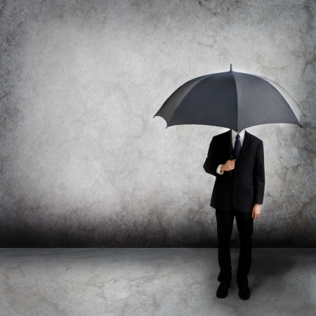 umbrella rain: Business man holding an umbrella