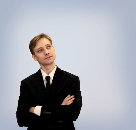 upwards: Young business in black suit looking upwards and thinking