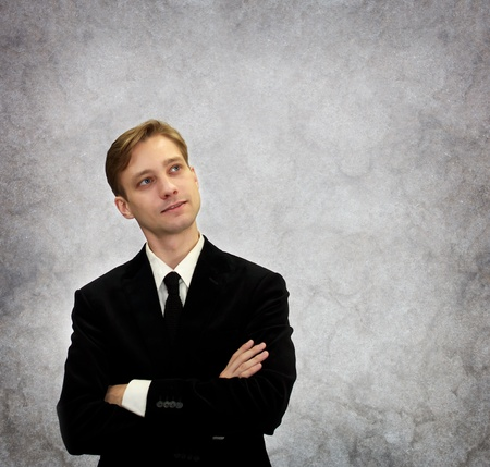 Young business in black suit looking upwards and thinking Stock Photo - 12270027