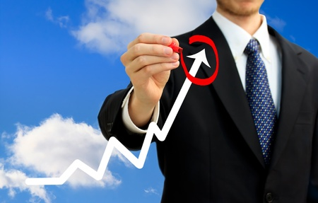 Businessman circling a rising arrow on a graph  representing growth