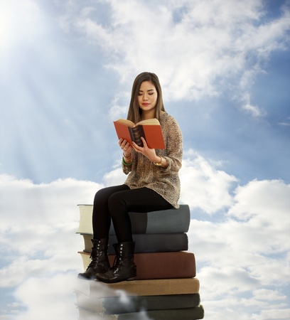 Beautiful Young Woman Reading a Book on Top of Books in the Clouds photo
