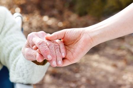 Senior Lady Händchen haltend mit jungen Hausmeister