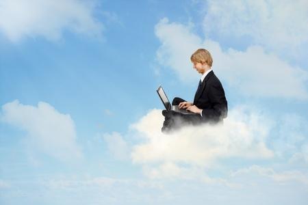 Jonge zakenman zittend op wolken en met behulp van een laptop