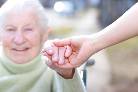old age care: Senior Lady in Wheelchair and Young Woman Holding Hands Outside