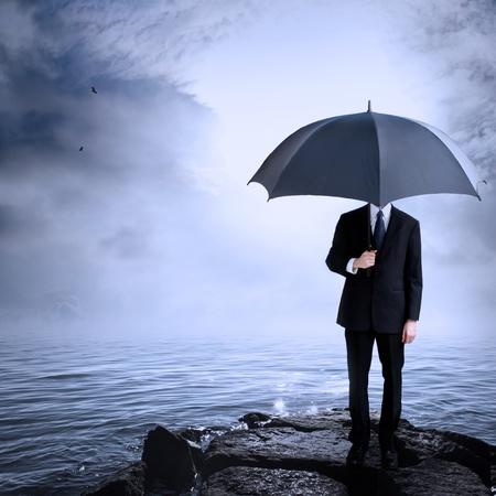 hombre solitario: Hombre de negocios que sostiene el paraguas en la costa después o antes de una tormenta Foto de archivo