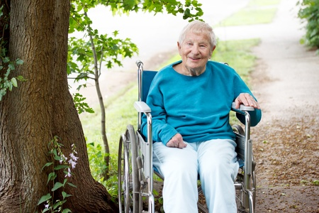 personas discapacitadas: Mujeres mayores en una silla de ruedas sonriente fuera