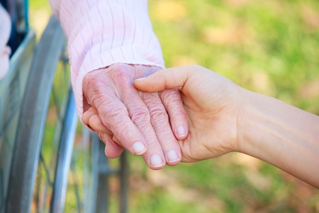 Senior Lady in Wheelchair Holding Hands with a Young Caretaker or Loved-one Stock Photo